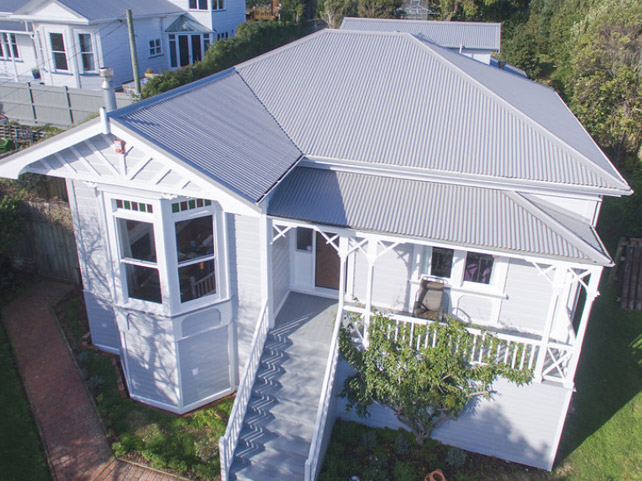 A wide shot of a white weatherboard home with grey metal roofing.